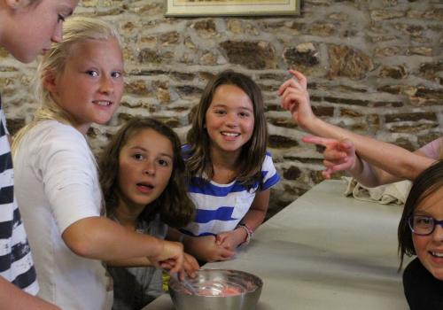 groupe de filles souriantes qui preparent la pate a cup cakes